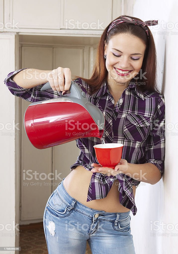 pretty housewife girl pours water into cup royalty-free stock photo