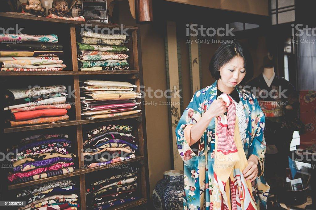 Pretty Japanese Woman Choosing Yellow Kimono in Kyoto, Japan stock photo