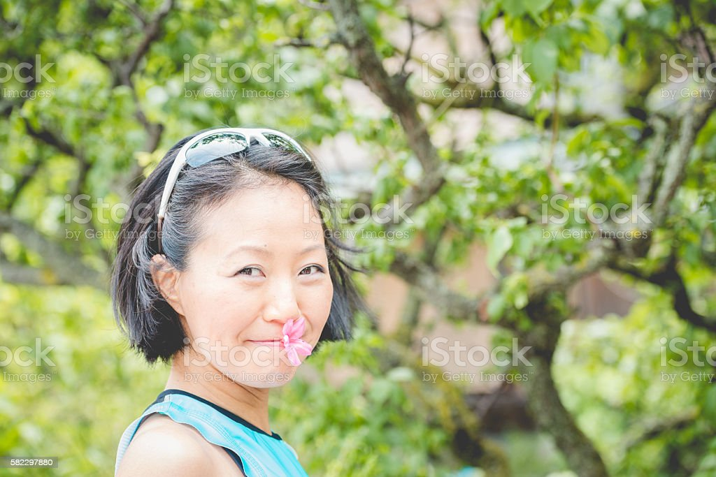 Pretty Japanese Woman with Rhododendron Blossom in Mouth, Kyoto, Japan stock photo