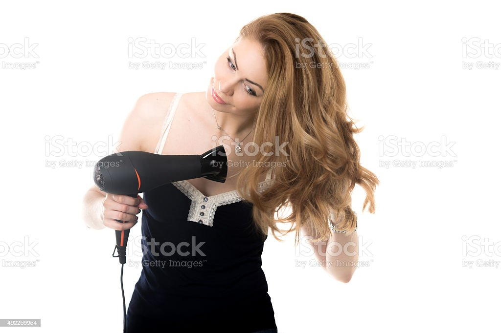 Pretty lady drying her hair with fen stock photo
