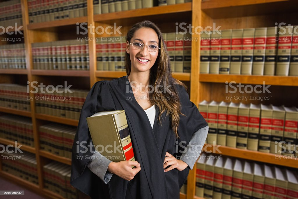 Pretty lawyer looking at camera in the law library stock photo