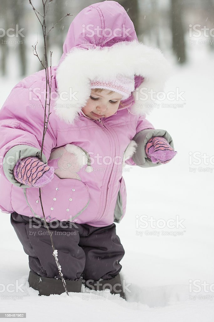 Pretty little baby girl playing in a snowy winter park royalty-free stock photo