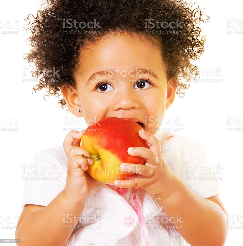 Pretty little girl biting an apple stock photo