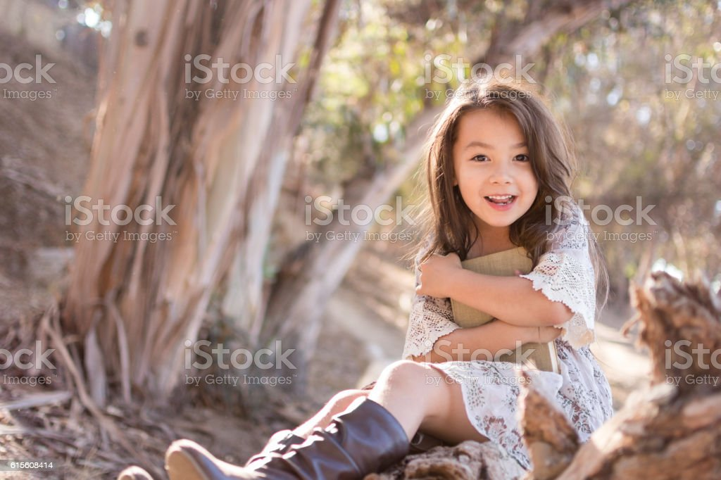 Pretty little girl outdoors excited about reading a book stock photo