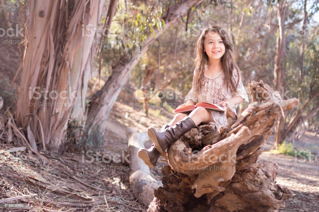 Pretty little girl outdoors happily reading a book stock photo