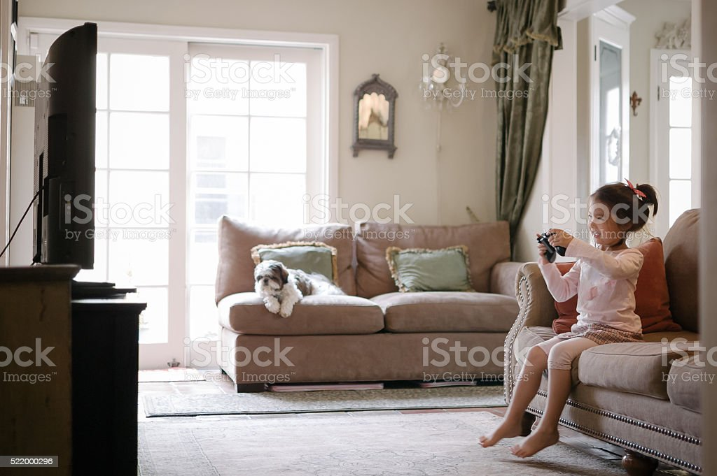 Pretty little girl playing a video game at home stock photo