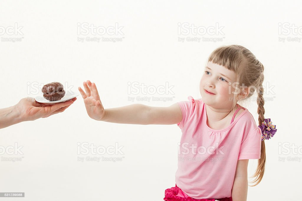 Pretty little girl reоecting a chocolate cake stock photo