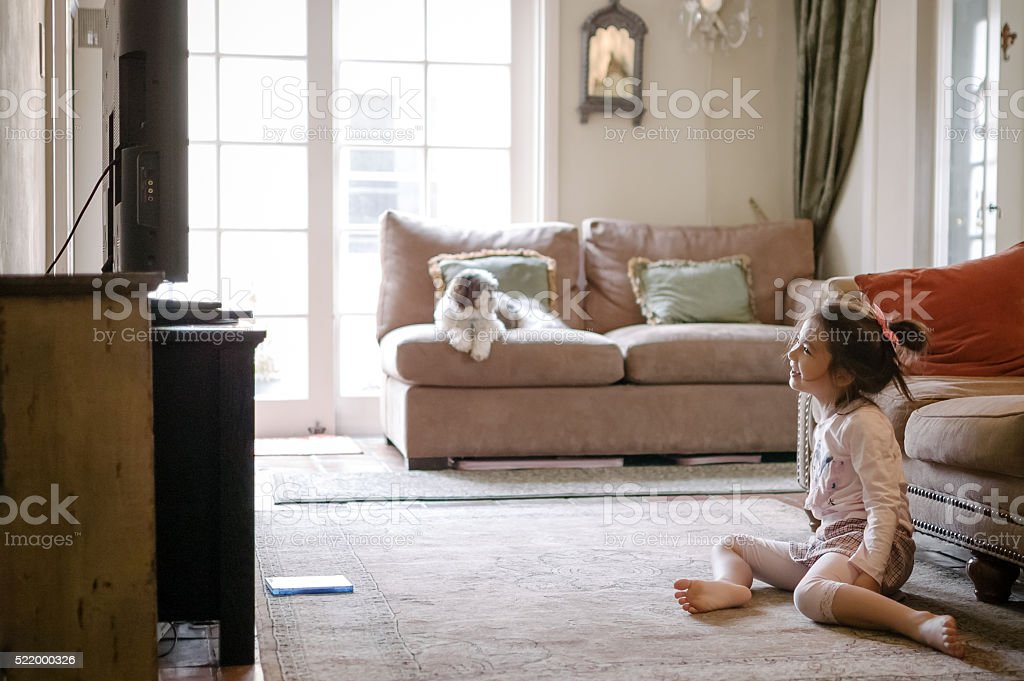 Pretty little girl watching a DVD on TV at home stock photo
