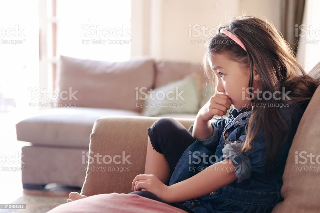 Pretty little girl watching TV on the couch stock photo