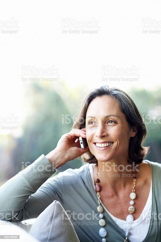 Pretty, mature woman enjoying a conversation on phone royalty-free stock photo