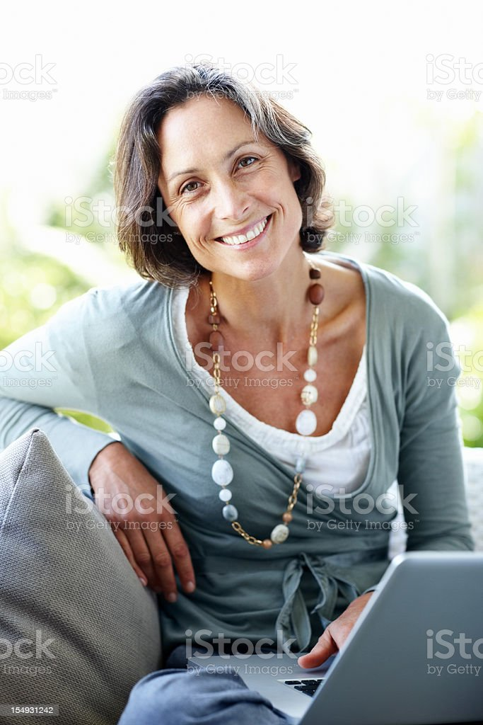 Pretty, mature woman sitting at home with laptop royalty-free stock photo
