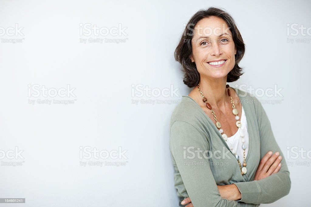 Pretty, mature woman standing with her hands folded stock photo