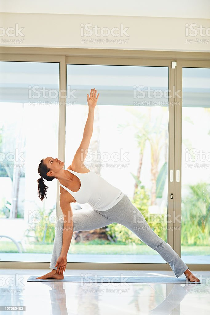 Pretty middle aged female doing yoga exercise on mat royalty-free stock photo