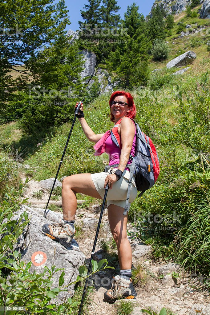 Pretty middle aged female hiker resting on big rock stock photo