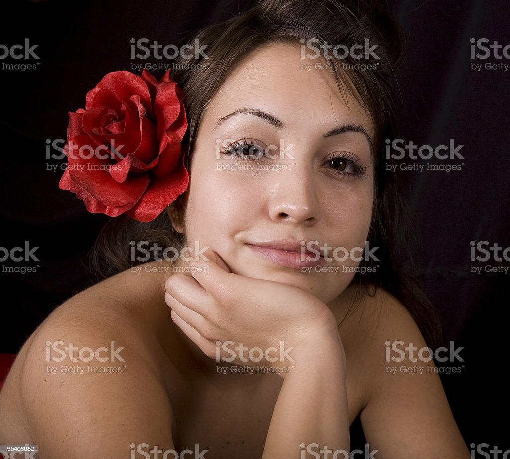 Pretty model with red flower in her hair stock photo