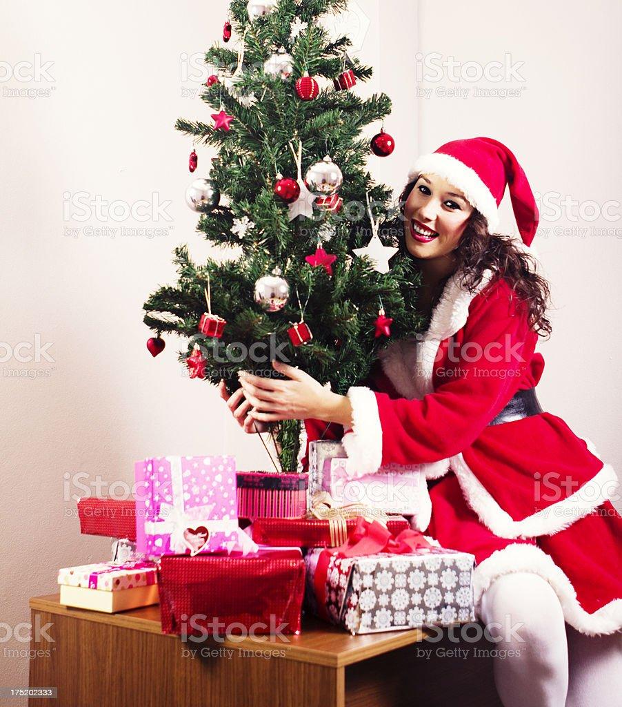 Pretty Mrs.Claus hugging christmas tree royalty-free stock photo