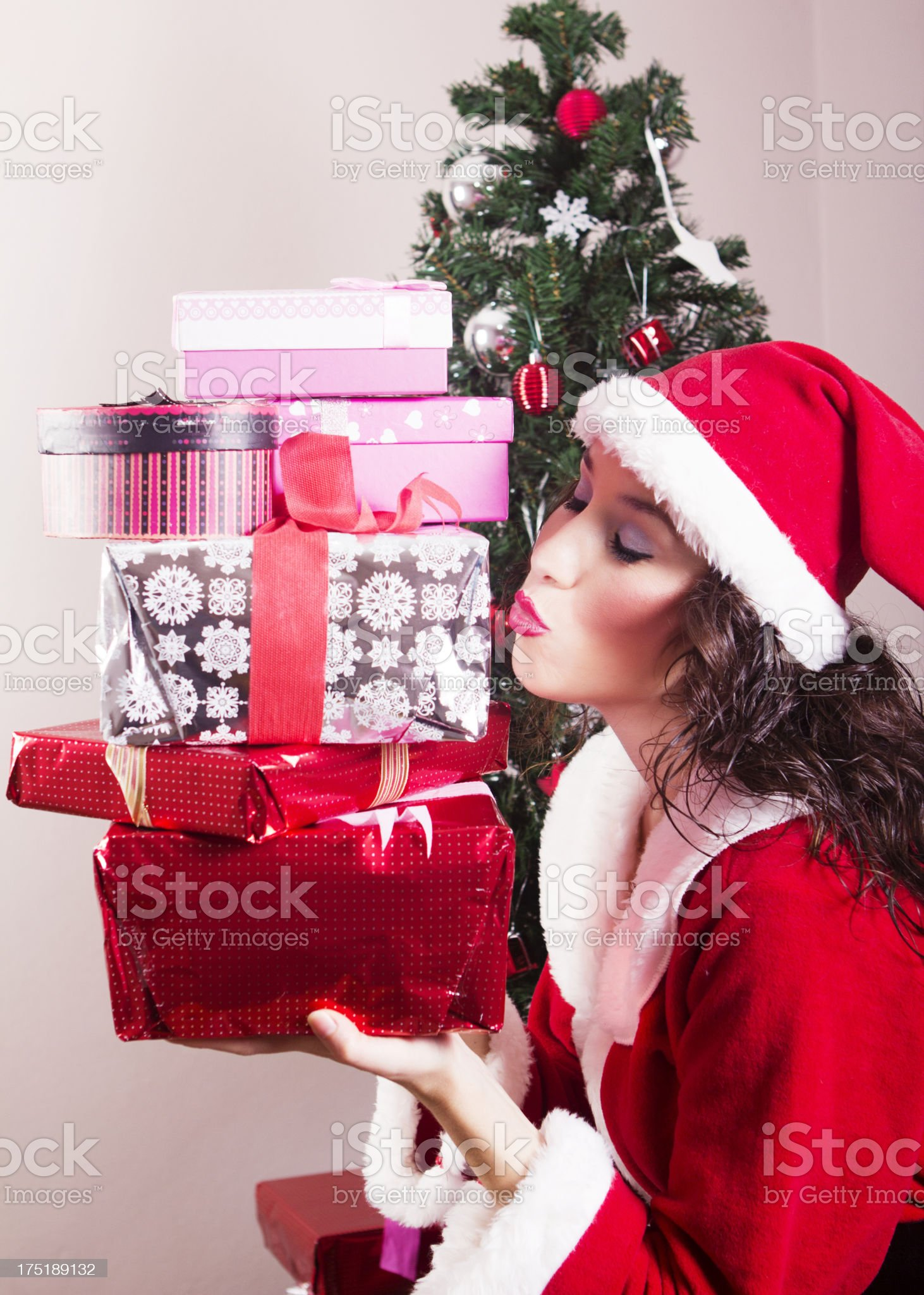 Pretty Mrs.Claus kissing gift boxes royalty-free stock photo
