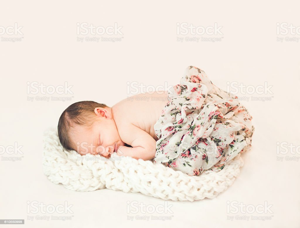 Pretty newborn sleeping baby isolated from background stock photo