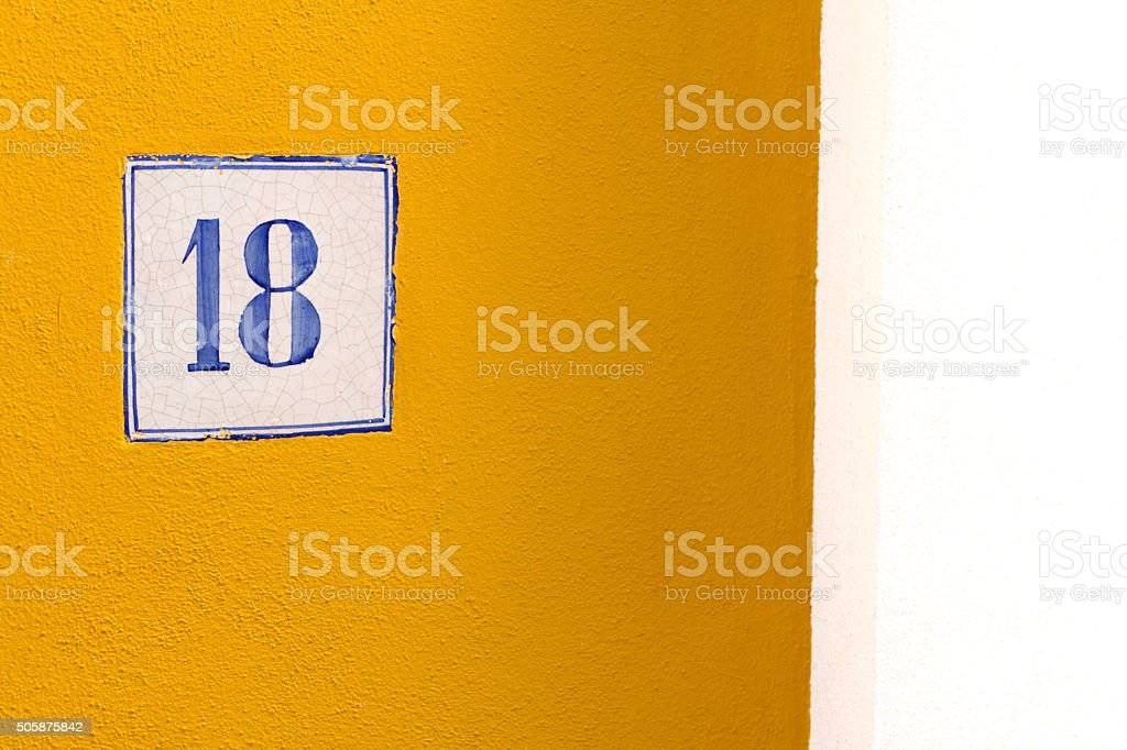 Pretty Number 18 Street Plaque On Yellow Stucco Wall stock photo