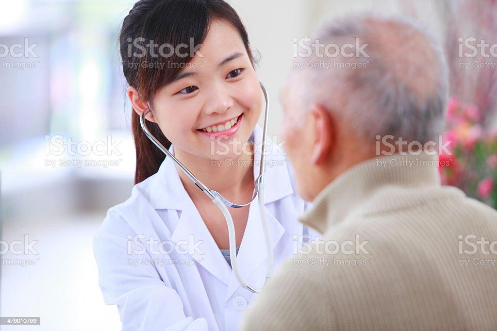pretty nurse doing health check to senior man stock photo