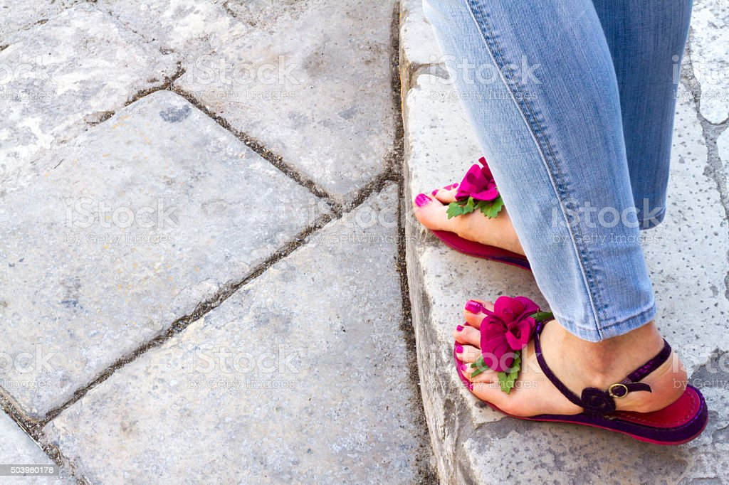 Pretty Pedicured Feet in Flowery Sandals, Jeans, Cobblestones stock photo