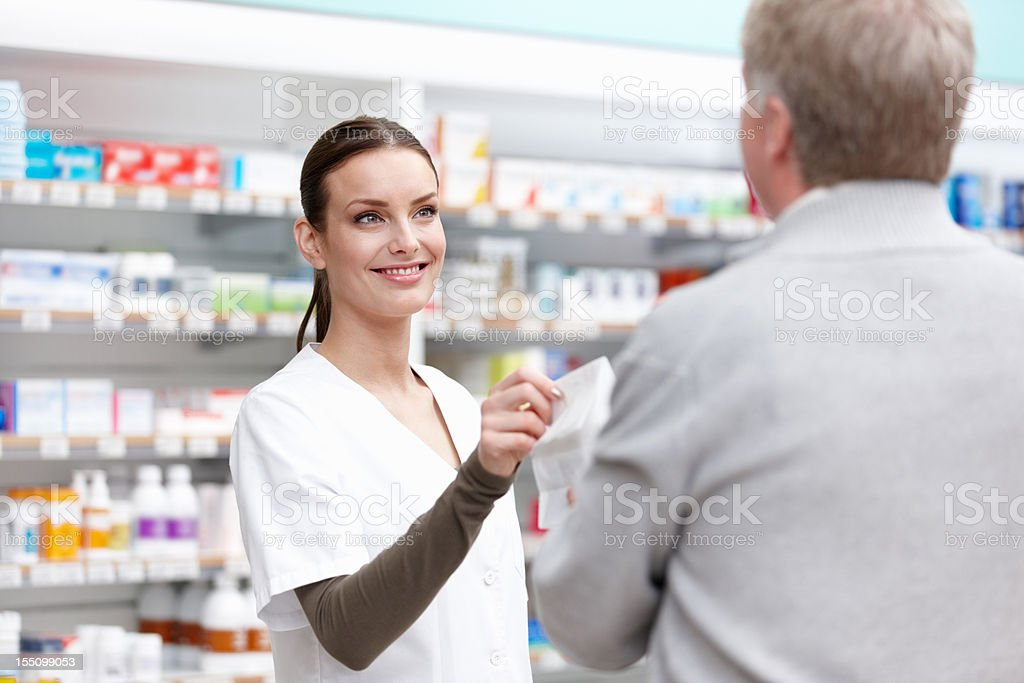 Pretty pharmacist giving a package royalty-free stock photo