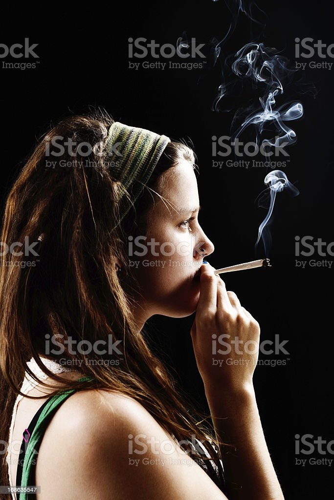 Pretty pot head thoughtfully smoking marijuana joint. stock photo
