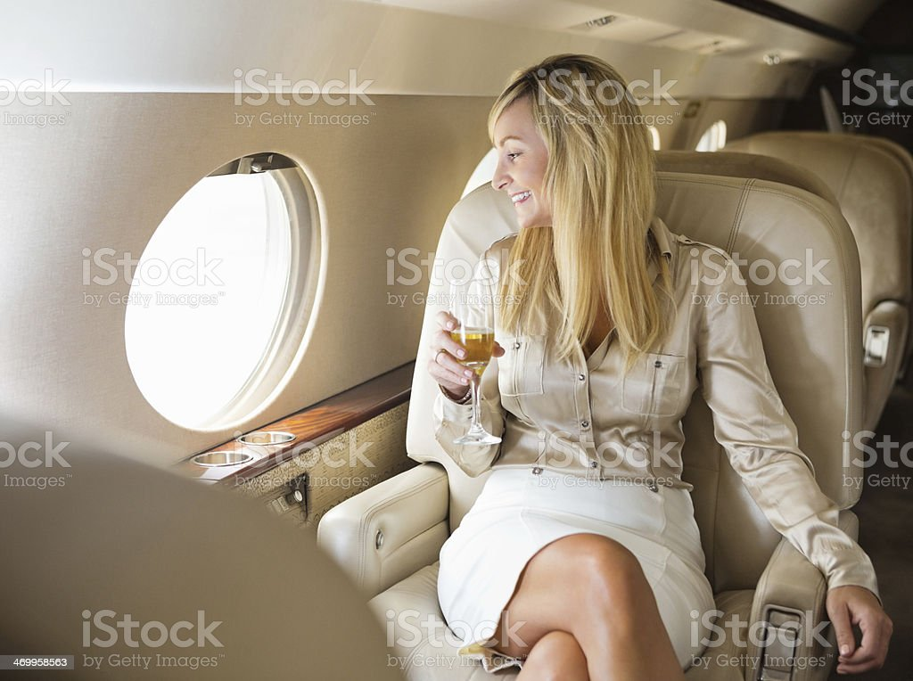 Pretty professional woman drinking champagne on board private jet stock photo