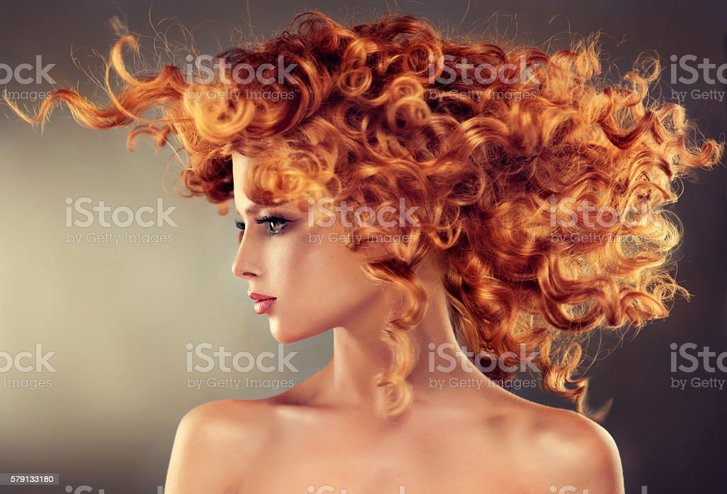 Pretty red haired girl with curly hairstyle. stock photo