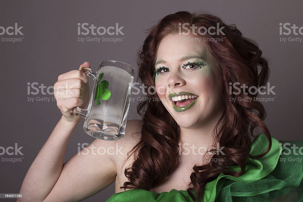 Pretty red headed woman drinking from Mug with a shamrock stock photo
