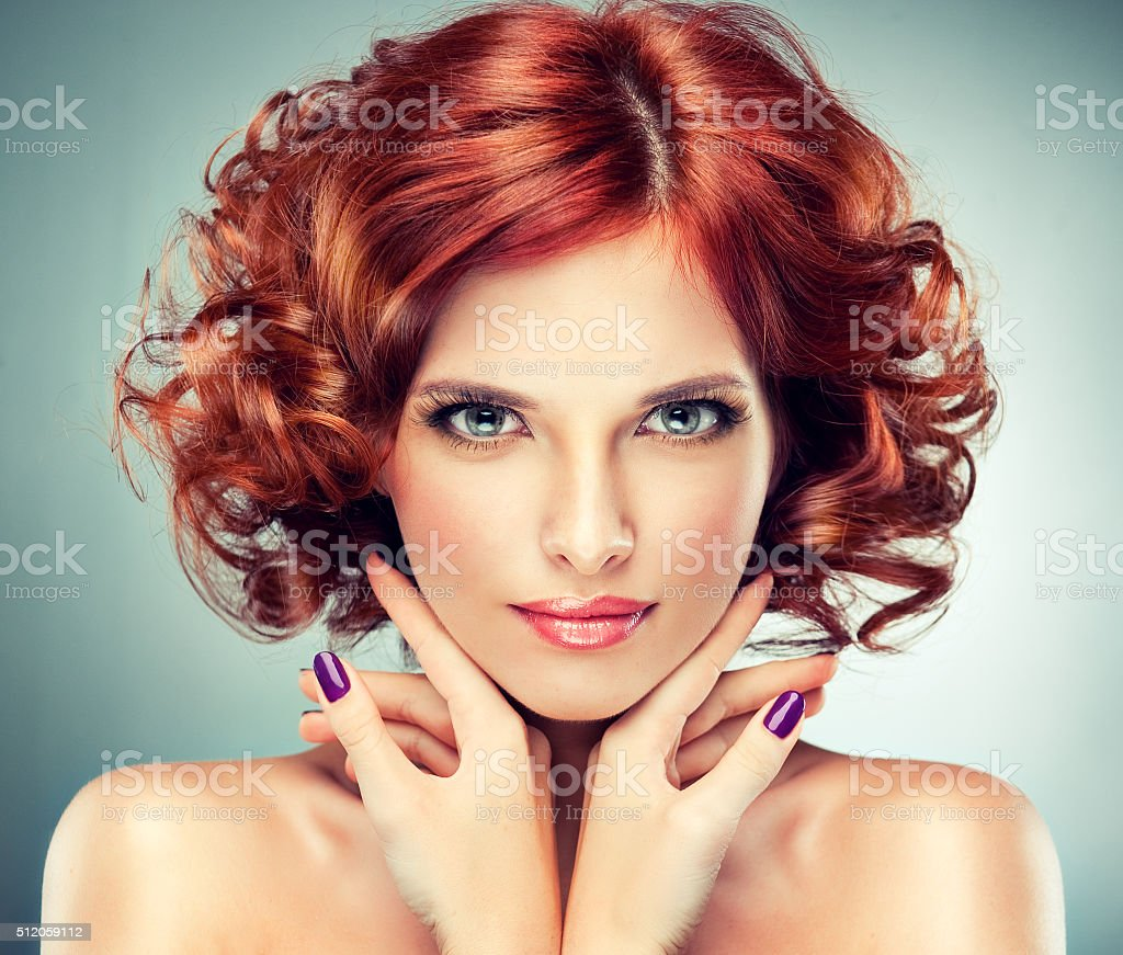Pretty red-haired girl with curls and fashionable make-up. stock photo