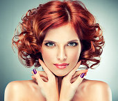 Pretty red-haired girl with curls and fashionable make-up.