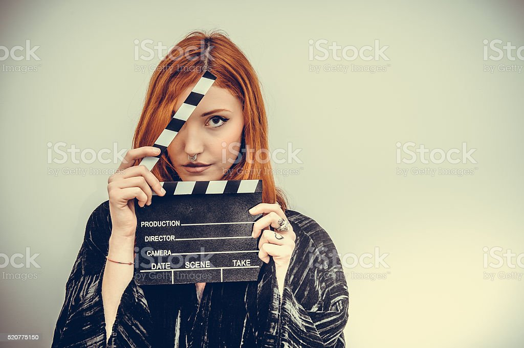 Pretty redhead actress with movie clapper board stock photo