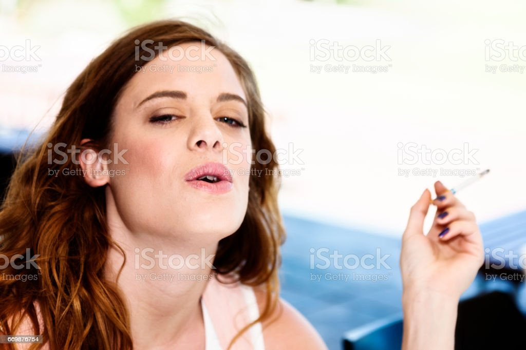 Pretty redhead blowing cigarette smoke smiles knowingly stock photo