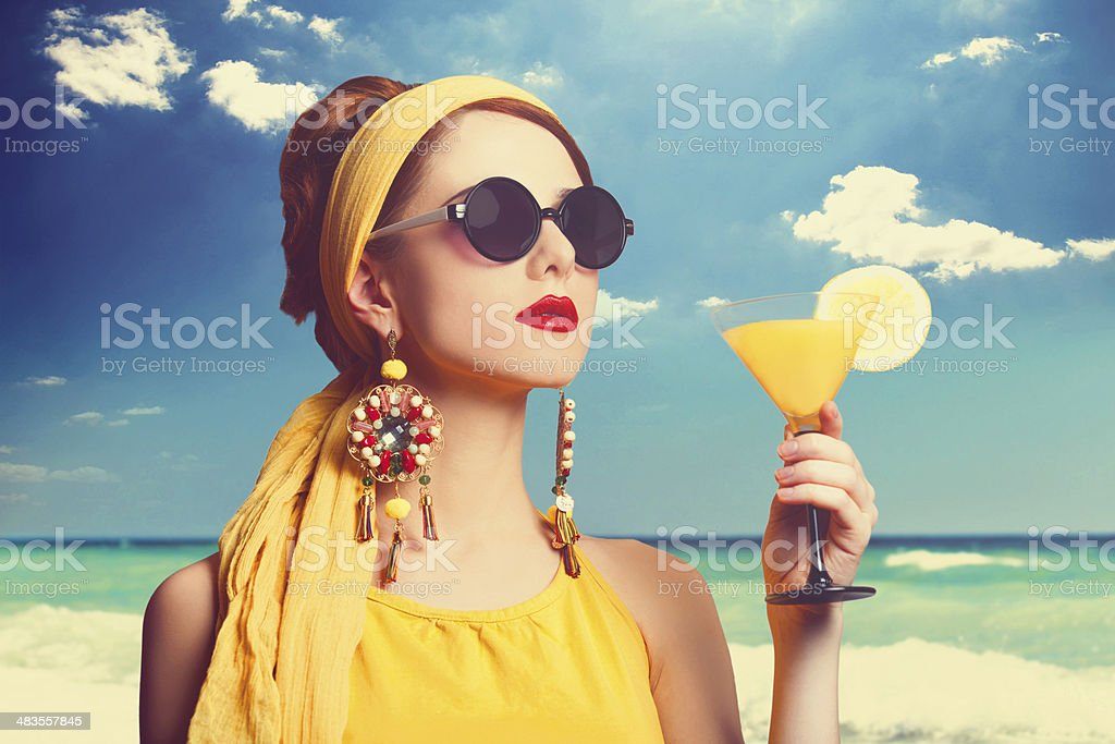 Pretty redhead women with cocktail on the beach. stock photo