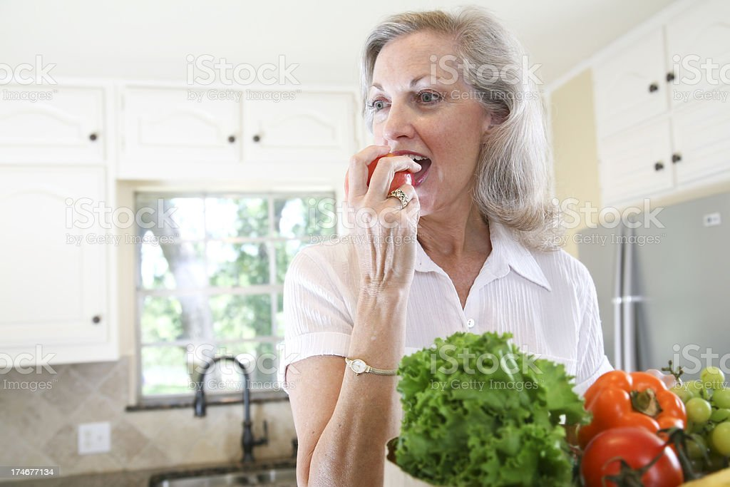 Pretty Senior Adult Woman Eating an Apple in her Kitchen stock photo