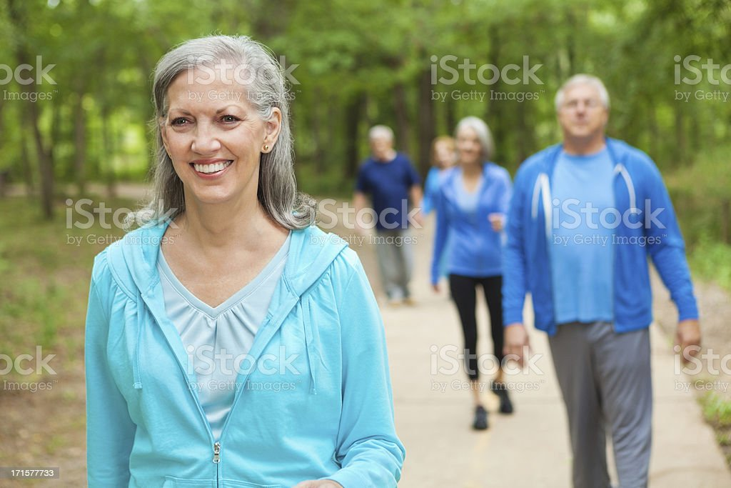 Pretty senior woman walking in park with exercise group royalty-free stock photo