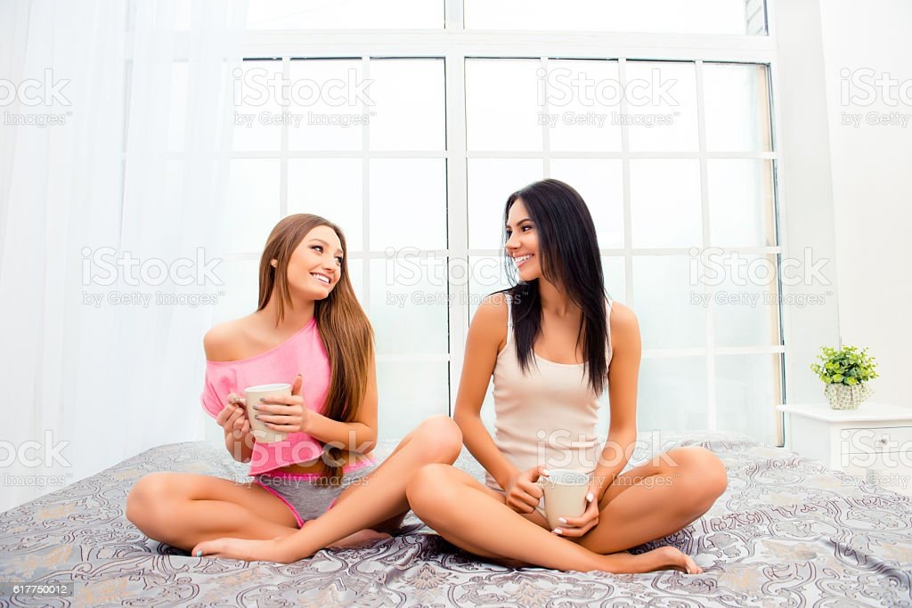 Pretty sexy  girls drinking coffee and sitting on bed stock photo