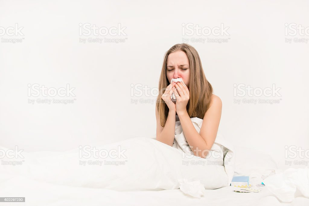 Pretty sick woman lying in bed and having grippe stock photo