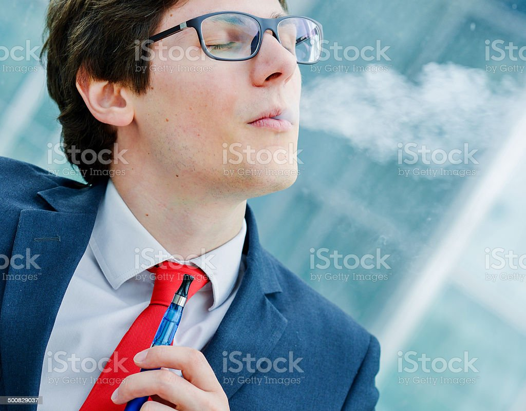 Pretty single man inhaling from an electronic cigarette royalty-free stock photo