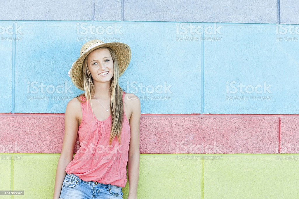 A pretty, smiling, blond girl stands in the summer sun. royalty-free stock photo