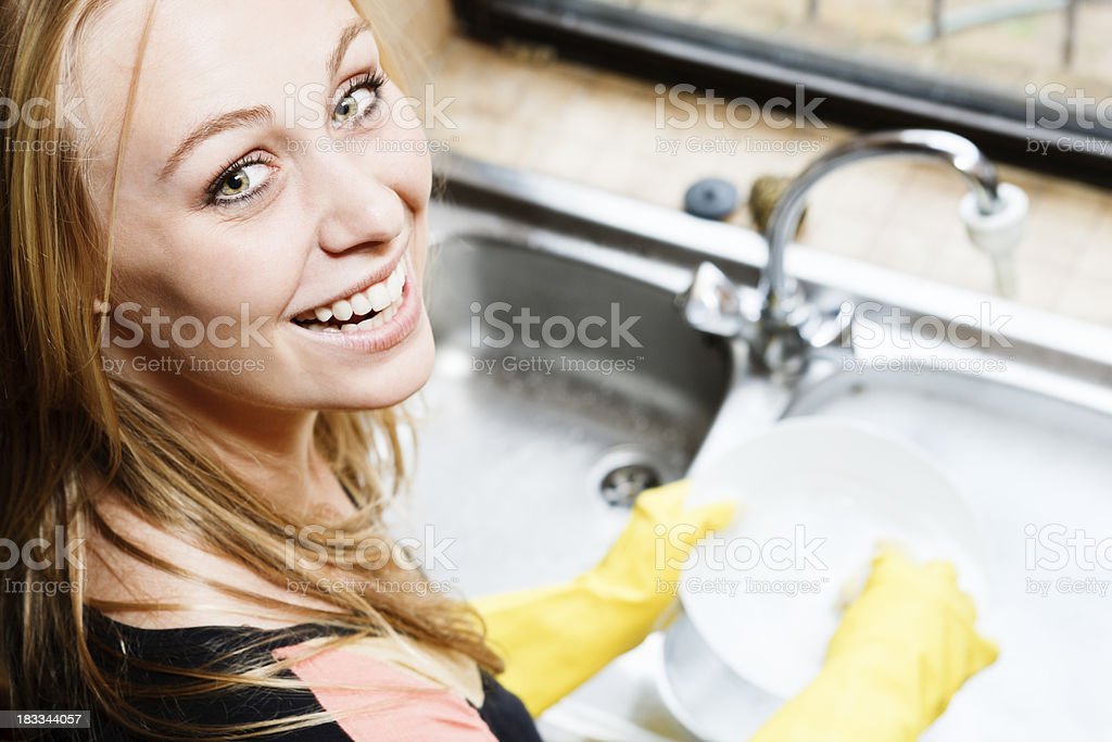 Pretty, smiling blonde looks round from doing the dishes stock photo