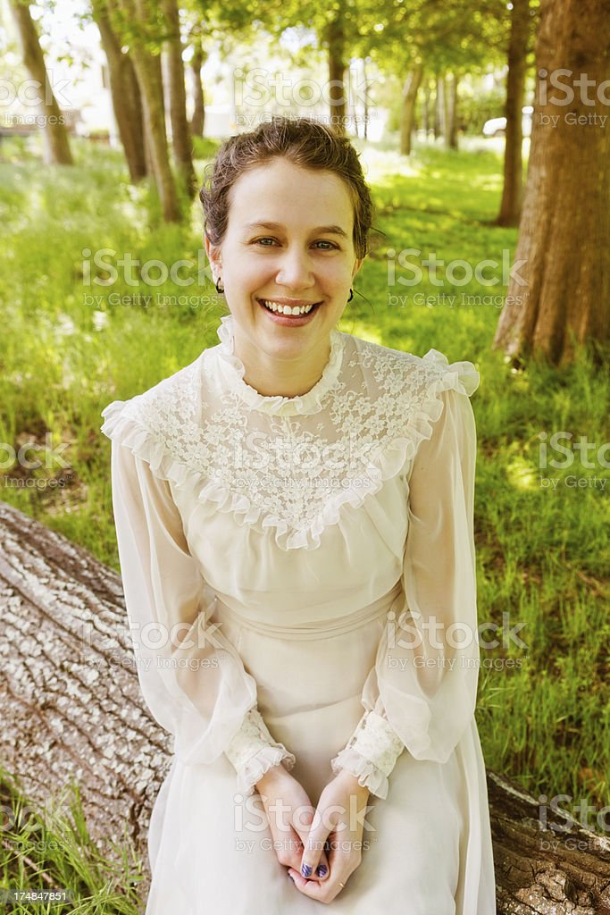 Pretty, smiling brunette wearing Victorian-style dress smiles in forest clearing royalty-free stock photo
