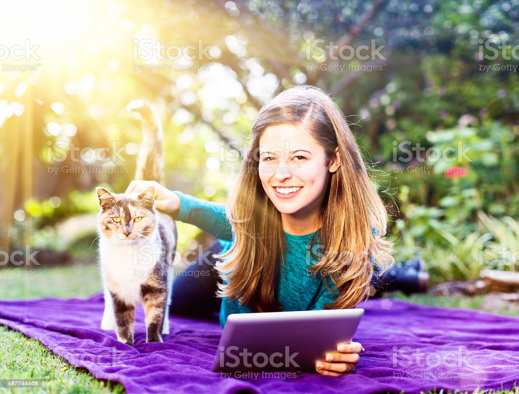 Pretty smiling girl relaxing in garden with pet cat stock photo