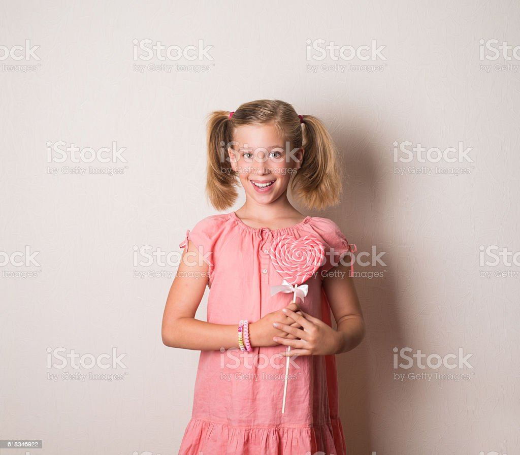 Pretty smiling girl with big heart shaped lollipop stock photo