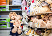 Pretty smiling little girl with teddy-bear in grocery store