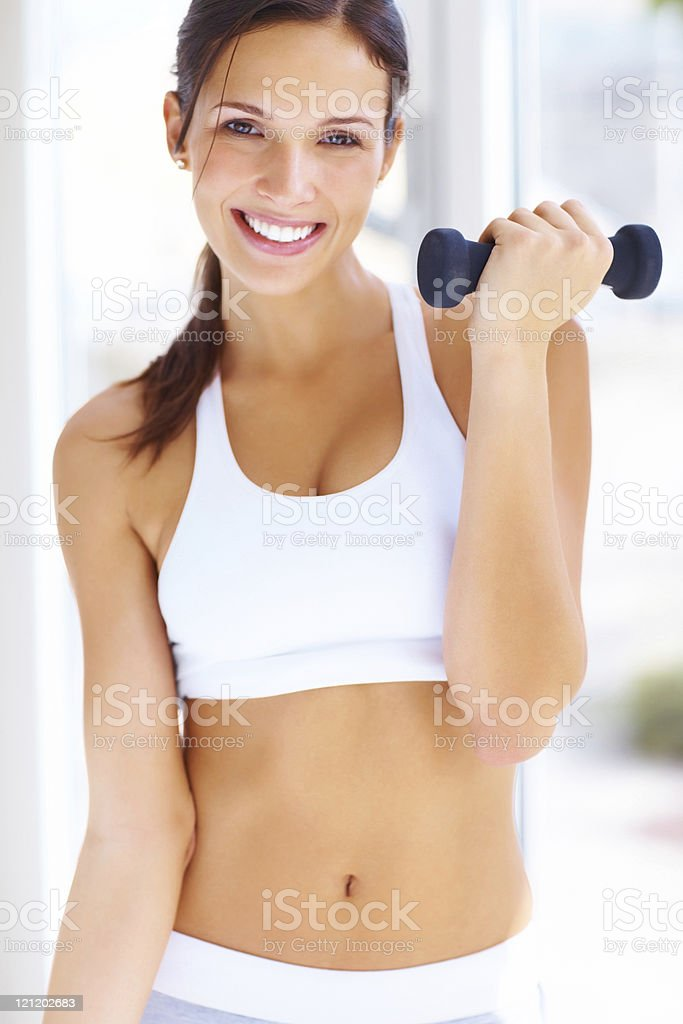Pretty smiling woman exercising with free weights royalty-free stock photo