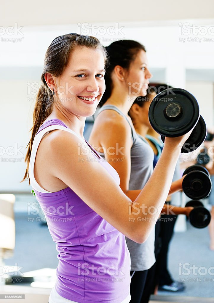 Pretty smiling young woman lifting weights in gym stock photo