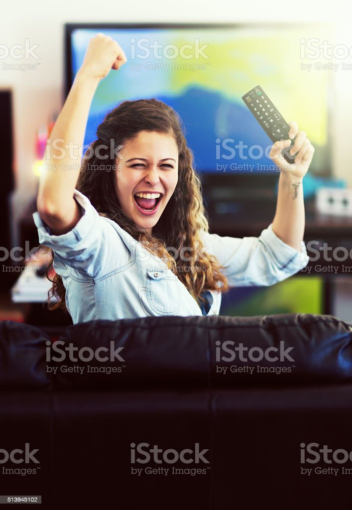 Pretty sports enthusiast holds TV remote, cheering her team stock photo