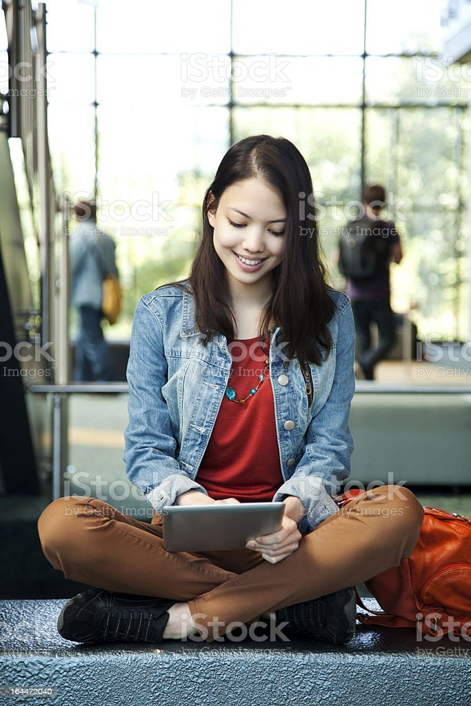 Pretty student using a digital tablet royalty-free stock photo